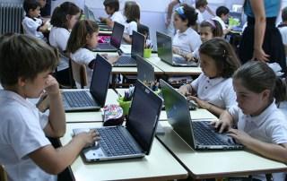 Niños con portátiles en un aula