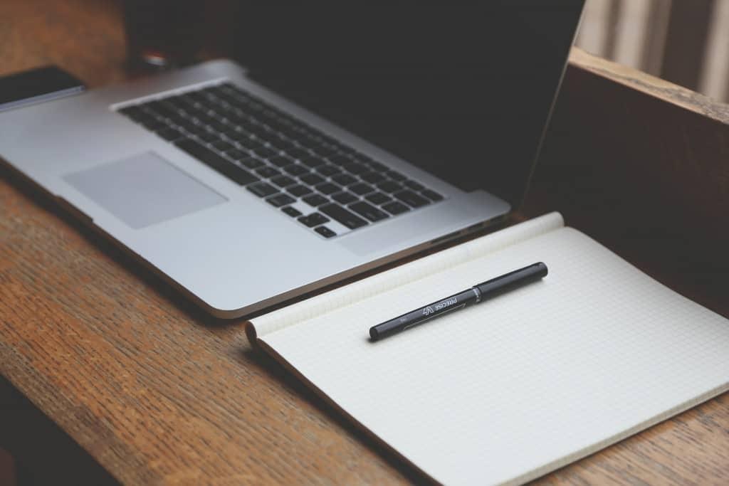 Ordenador y cuaderno listos para escribir un texto argumentativo